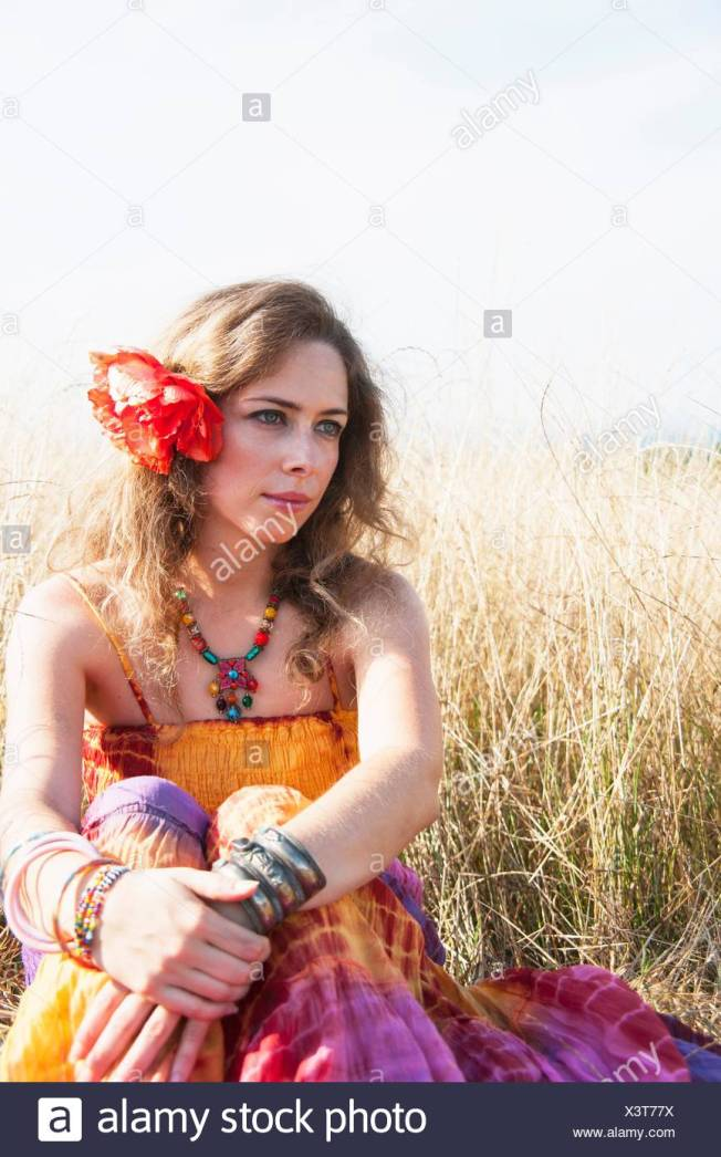 portrait-of-mid-adult-woman-in-hippy-clothes-sitting-in-field-X3T77X